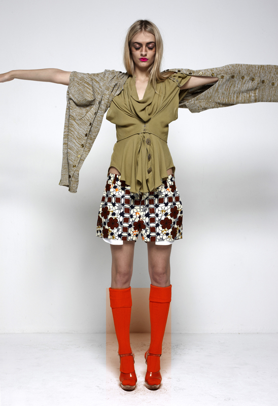 Future Classics fashion SS12 collection: Afrika E8 Look 15 Abstract Shrug Olive Marl Cotton Knitwear with Pale Olive Silk Double Front Cape Blouse and African Print Shorts